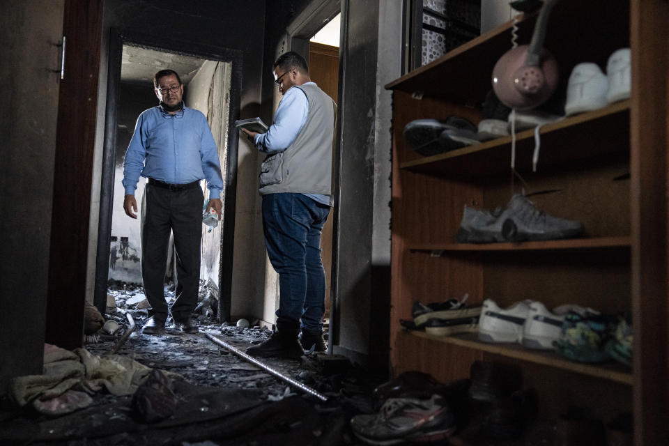 Mohammed Elfarawi, left, speaks to Khalid Sbitan, a human rights worker for Al Mezan Center for Human Rights, right, in the severely damaged room that belonged to his son Adam who was killed when an airstrike targeted the apartment below prior to a cease-fire that halted an 11-day war between Gaza's Hamas rulers and Israel, Thursday, May 27, 2021, in Gaza City. (AP Photo/John Minchillo)