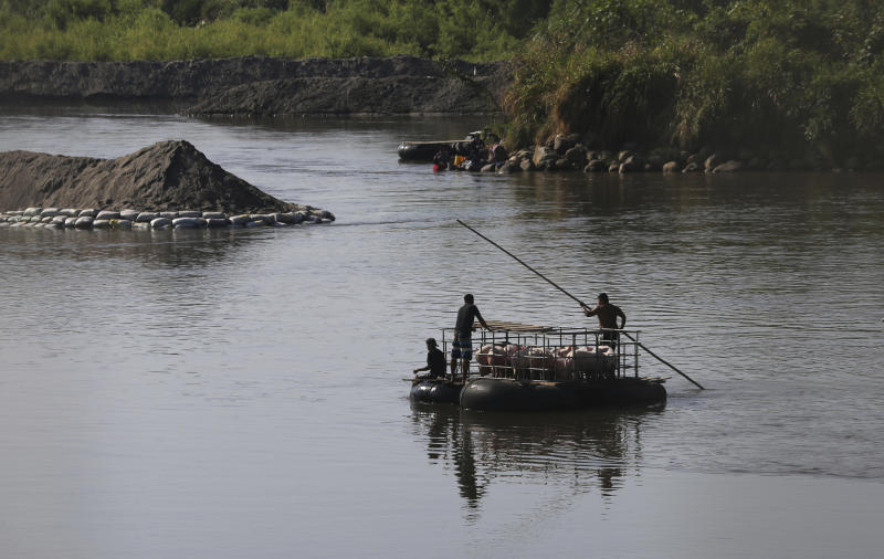 Men transport pigs across the Suchiate River, from Mexico to Guatemala, as they move away from Ciudad Hidalgo, Mexico, Friday, Jan. 24, 2020, a location popular for migrants to cross from Guatemala to Mexico. (AP Photo/Marco Ugarte)
