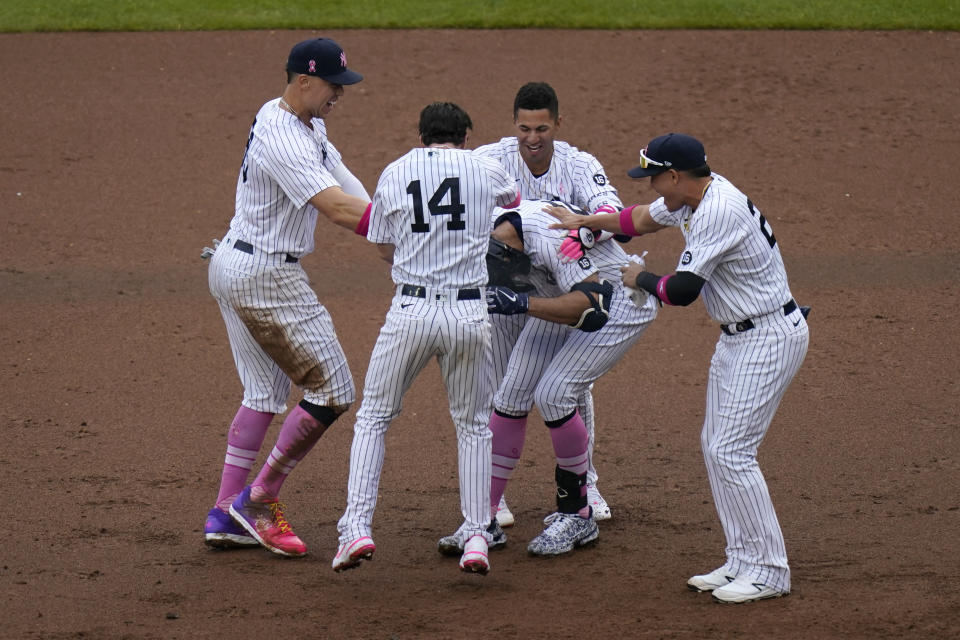 Teammates mob New York Yankees' Giancarlo Stanton, center, after he hit a walkoff single during the ninth inning of a baseball game against the Washington Nationals at Yankee Stadium, Sunday, May 9, 2021, in New York. (AP Photo/Seth Wenig)