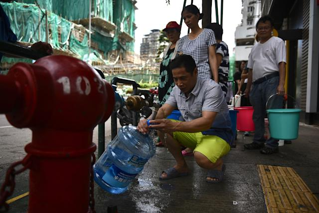 <p>Residents queue up for water from a fire hydrant on a pavement in Macau on Aug. 24, 2017, a day after Typhoon Hato hit the city causing power outages and a water shortage. (Photo: Anthony Wallace/AFP/Getty Images) </p>