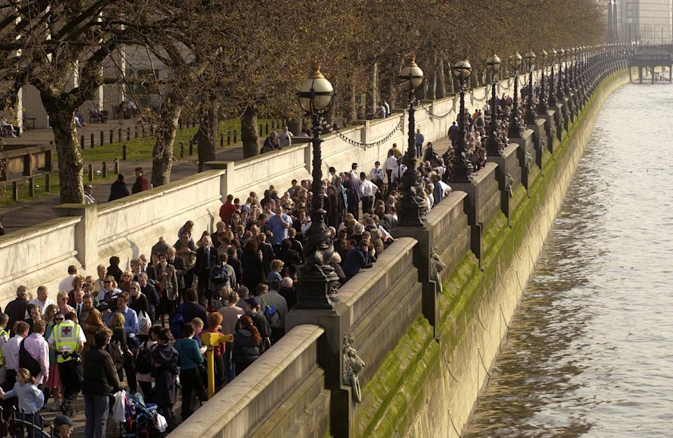LONDON, UNITED KINGDOM:  Mourners queue-up on the over bank of the river Thames to get to Westminster Hall where the Queen mother's coffin lies in-state in London 05 april 2002. Westminster Hall will remain open to the public. AFP PHOTO NICOLAS ASFOURI (Photo credit should read NICOLAS ASFOURI/AFP via Getty Images)