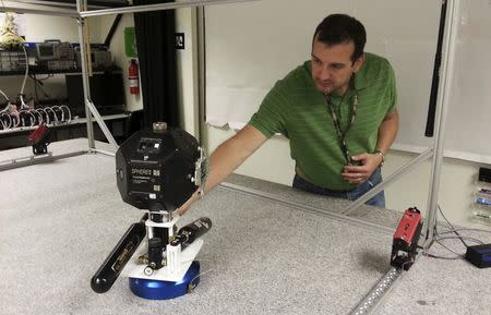 Smart SPHERES project manager Chris Provencher demonstrates one of NASA's robots at the Ames Research Center in Mountain View, California July 2, 2014. REUTERS/Noel Randewich