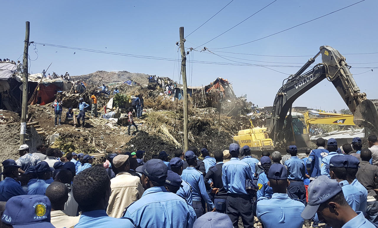 <p>Police officers secure the perimeter at the scene of a garbage landslide, as excavators aid rescue efforts, on the outskirts of the capital Addis Ababa, Ethiopia Sunday, March 12, 2017. Officials and residents say more than a dozen people have been killed in a landslide at a massive garbage dump on the outskirts of Ethiopia's capital, and several dozen people are missing. (AP Photo/Elias Meseret) </p>