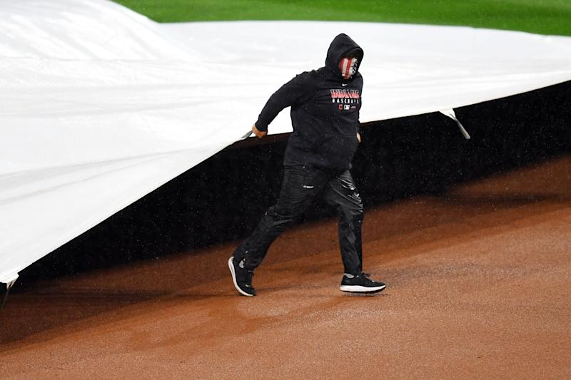 A member of the grounds crew pulls the tarp on the field during a rain delay during Game 2 of the wild-card series in Cleveland. (Photo by Joe Sargent/MLB Photos via Getty Images)