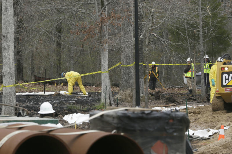 Crews work to clean up from an oil pipeline spill in a Mayflower, Ark., neighborhood Wednesday, April 3, 2013.  An ExxonMobil pipeline ruptured last week and spewed thousands of barrels of crude oil.  (AP Photo/Danny Johnston)