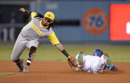 FILE PHOTO: Aug 25, 2018; Los Angeles, CA, USA; San Diego Padres shortstop Freddy Galvis (left) tags out Los Angeles Dodgers shortstop Manny Machado (8) attempting to steal second base during the seventh inning at Dodger Stadium. Mandatory Credit: Orlando Ramirez-USA TODAY Sports