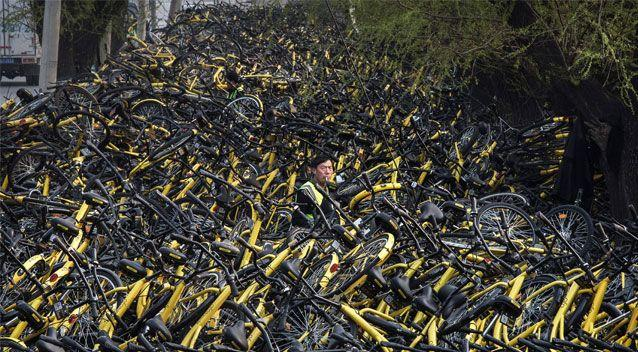 One worker struggles to keep on top of the escalating number of bikes. Source: Getty
