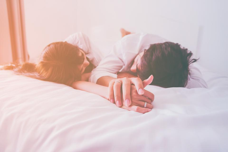 Couple in love holding hands sleep in the bed with sunlight in the morning