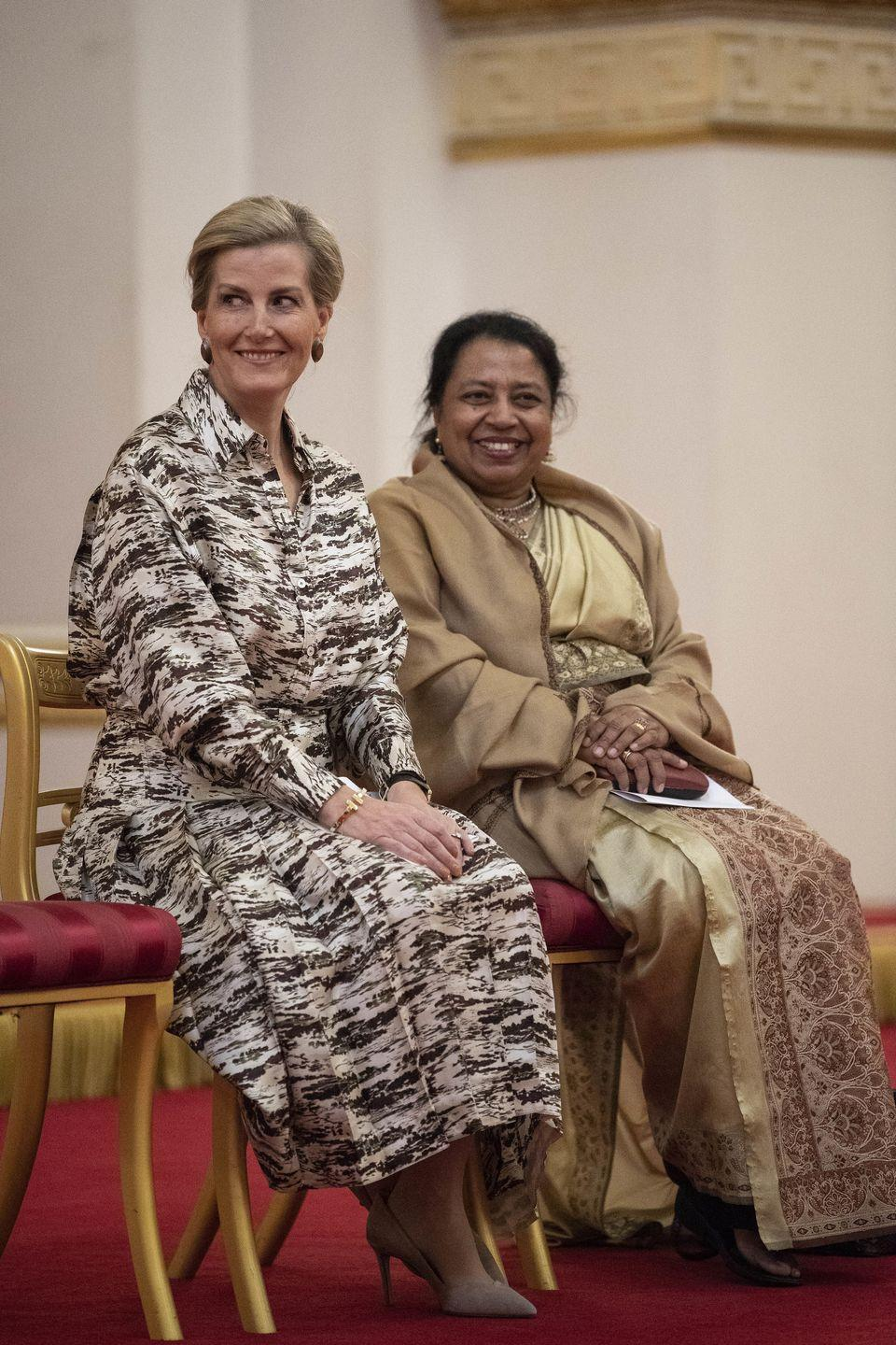 <p>The Countess of Wessex changed into a long-sleeve brown and white patterned dress (although she continued to wear the same earrings and heels) to host a reception at Buckingham Palace in honor of International Women's Day. </p>