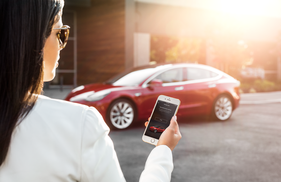 A woman using a Tesla mobile app to unlock Model 3.