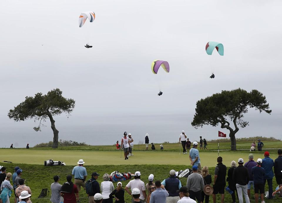 Paragliders fly near the fourth hole during the second round of the U.S. Open.