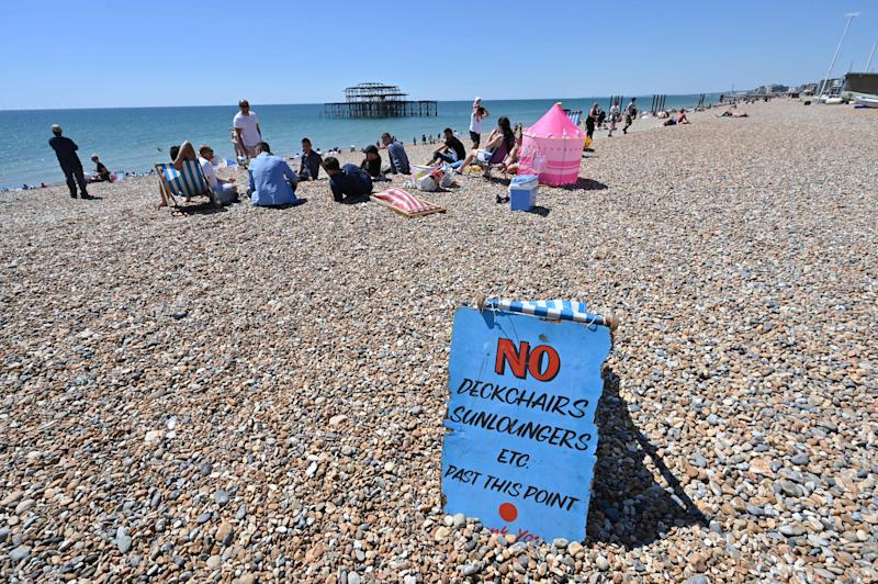 TOPSHOT - People sunbathe on the beach in front of the derelict West Pier in Brighton, on the south coast of England on May 31, 2020 on the eve of a further relaxation of the novel coronavirus lockdown rules. - The UK government has set out a gradual easing of lockdown measures in England, with socially distanced groups of six friends and families allowed to meet in parks and gardens from June 1. (Photo by Glyn KIRK / AFP) (Photo by GLYN KIRK/AFP via Getty Images)