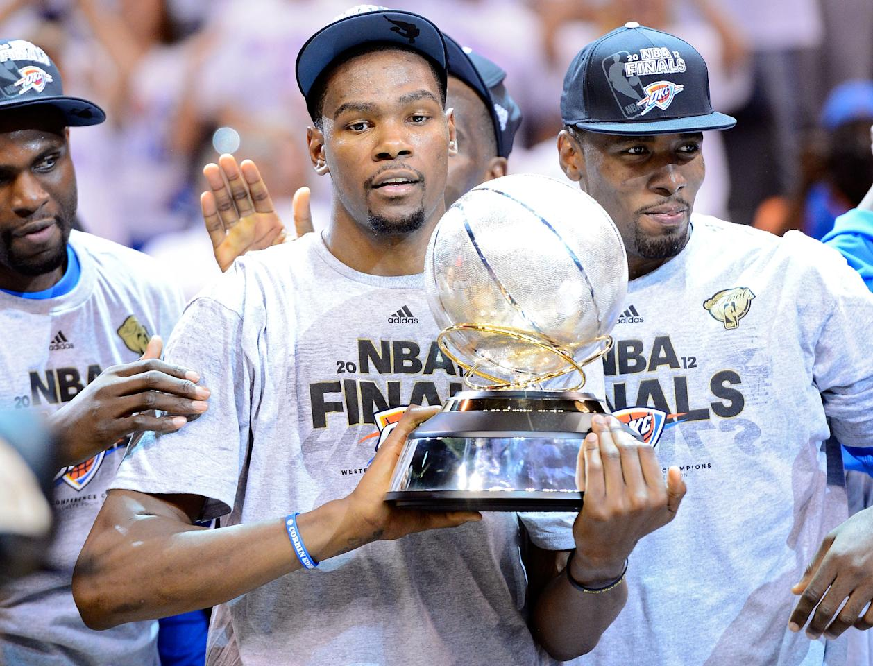 OKLAHOMA CITY, OK - JUNE 06:  Kevin Durant #35 of the Oklahoma City Thunder celebrates with the trophy after defeating the San Antonio Spurs to win the Western Conference Finals of the 2012 NBA Playoffs at Chesapeake Energy Arena on June 6, 2012 in Oklahoma City, Oklahoma. NOTE TO USER: User expressly acknowledges and agrees that, by downloading and or using this photograph, User is consenting to the terms and conditions of the Getty Images License Agreement.  (Photo by Michael Heiman/Getty Images)