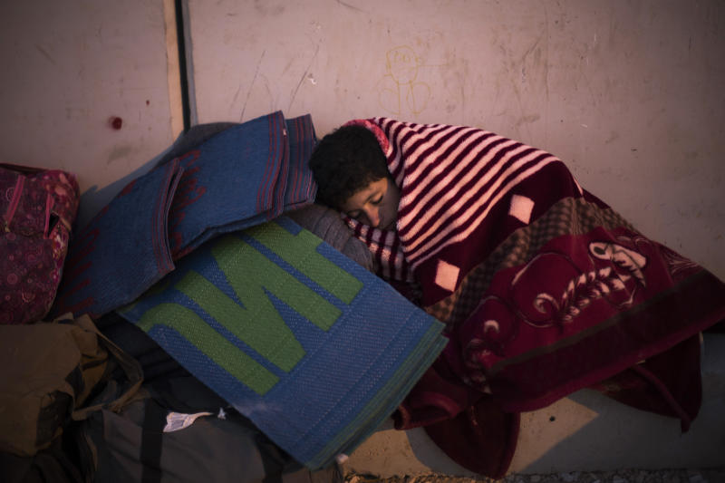 In this Thursday, Oct. 24, 2013, photo, a Syrian refugee sleeps covered with blankets at the new arrivals point at the Zaatari refugee camp near the Syrian border in Jordan. With Syria's civil war in its third year, more than 2 million Syrians have fled their country. About 100,000 live in this camp. (AP Photo/Manu Brabo)