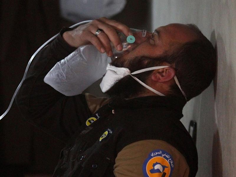 A White Helmets rescuer breathes through an oxygen mask, after a suspected gas attack in the town of Khan Sheikhoun, Idlib, on 4 April (Reuters)