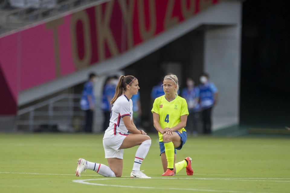 TOKYO, JAPAN - JULY 21:  Alex Morgan. #13 of the United States and Hanna Glas #4 of Sweden take a knee before the start of the USA V Sweden group G football match at Tokyo Stadium during the Tokyo 2020 Olympic Games on July 21, 2021 in Tokyo, Japan. (Photo by Tim Clayton/Corbis via Getty Images)