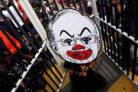 "FILE PHOTO: A student activist holds up a placard of Fahmi Reza's caricature of Najib Razak during a protest to call for the arrest of ""Malaysian Official 1"" in Kuala Lumpur"