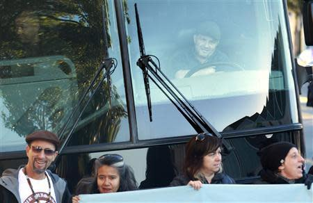 A bus driver, with workers from the technology industry, looks on from his bus as it is blocked during a protest against rising costs of living in San Francisco