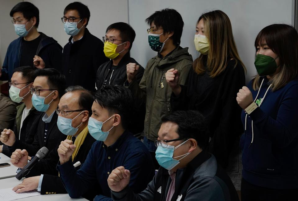 <p>Pro-democratic party members shout slogans in response to the mass arrests during a press conference in Hong Kong on 6 January</p> (AP)