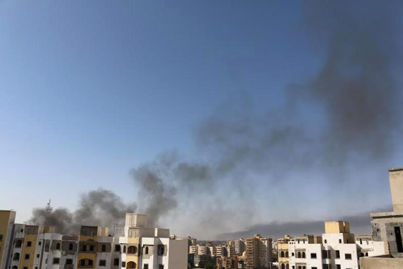 Smoke rises near buildings after heavy fighting between rival militias broke out near the airport in Tripoli