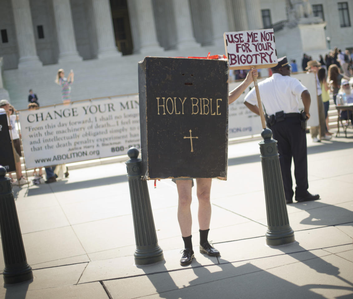 A demonstrator dressed as the 'Bible' stands outside the Supreme Court building awaiting the court's decision on the Hobby Lobby case in Washington, Monday, June 30, 2014. The Supreme Court says corporations can hold religious objections that allow them to opt out of the new health law requirement that they cover contraceptives for women.(AP Photo/Pablo Martinez Monsivais)