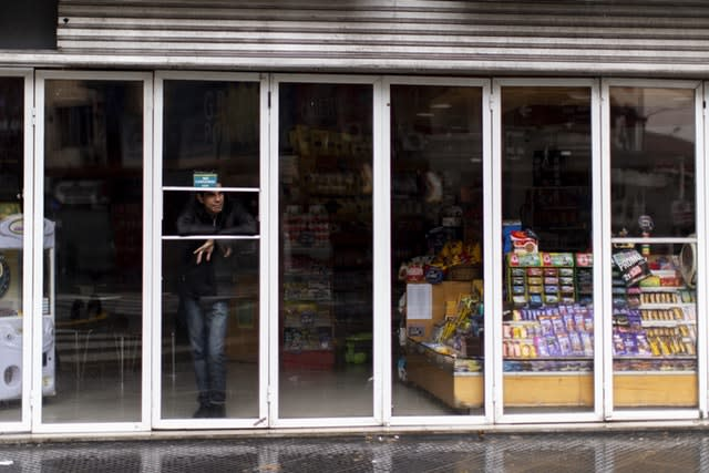 A man stands inside a shop without power