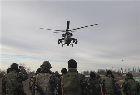 Russian army MI-35 military helicopter patrols the area as Ukrainian servicemen guard a checkpoint near the village of Strelkovo