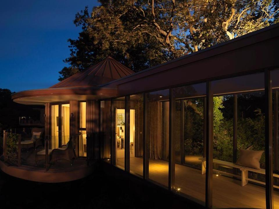 """<p>Arguably the most luxurious treehouse experience you can have in the UK, Chewton Glen's <a href=""""https://go.redirectingat.com?id=127X1599956&url=https%3A%2F%2Fwww.booking.com%2Fhotel%2Fgb%2Fchewtonglenhotel.en-gb.html%3Faid%3D2070929%26label%3Dhotels-with-cottages&sref=https%3A%2F%2Fwww.redonline.co.uk%2Ftravel%2Finspiration%2Fg35649846%2Fhotels-with-cottages%2F"""" rel=""""nofollow noopener"""" target=""""_blank"""" data-ylk=""""slk:Treehouse Suites"""" class=""""link rapid-noclick-resp"""">Treehouse Suites</a> open as self-catering rentals for April 2021. Here, you can literally sleep in the trees in a secluded valley of the New Forest. Each of the 14 self-contained Treehouses is suspended 35 feet above ground for an unforgettable, unique and relaxing getaway. </p><p>Floor-to-ceiling windows provide panoramic views and every need is brought straight to your door, from signature Chewton Glen food (such as the iconic cheese souffle) to picnic hampers with foraged jams and honey from the hotel grounds. You'll also have access to a kitchen to cook up your own meals, or you can wander to the Walled Garden for a pizza from the outdoor wood-fired oven.</p><p>Choose from the <a href=""""https://go.redirectingat.com?id=127X1599956&url=https%3A%2F%2Fwww.booking.com%2Fhotel%2Fgb%2Fchewtonglenhotel.en-gb.html%3Faid%3D2070929%26label%3Dhotels-with-cottages%23room_22861808&sref=https%3A%2F%2Fwww.redonline.co.uk%2Ftravel%2Finspiration%2Fg35649846%2Fhotels-with-cottages%2F"""" rel=""""nofollow noopener"""" target=""""_blank"""" data-ylk=""""slk:Treehouse Loft"""" class=""""link rapid-noclick-resp"""">Treehouse Loft</a>, perfect for large households, with its two double beds and two singles, or the <a href=""""https://go.redirectingat.com?id=127X1599956&url=https%3A%2F%2Fwww.booking.com%2Fhotel%2Fgb%2Fchewtonglenhotel.en-gb.html%3Faid%3D2070929%26label%3Dhotels-with-cottages%23room_22861809&sref=https%3A%2F%2Fwww.redonline.co.uk%2Ftravel%2Finspiration%2Fg35649846%2Fhotels-with-cottages%2F"""" rel=""""nofollow noopener"""" target=""""_blank"""" data-yl"""