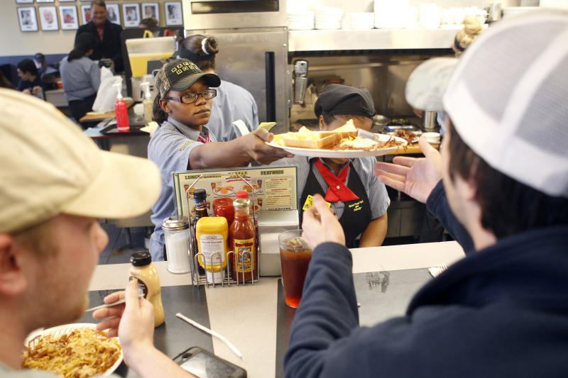 Waffle House server Tootie serves customers at a packed restaurant after residents spent two days cooped up due to an ice storm in downtown Atlanta, Georgia, February 13, 2014. A rare winter storm continued its grip on the U.S. South on Thursday, with over 300,00 people without power in Georgia as the storm moved up the east coast. REUTERS/Tami Chappell (UNITED STATES - Tags: ENVIRONMENT)