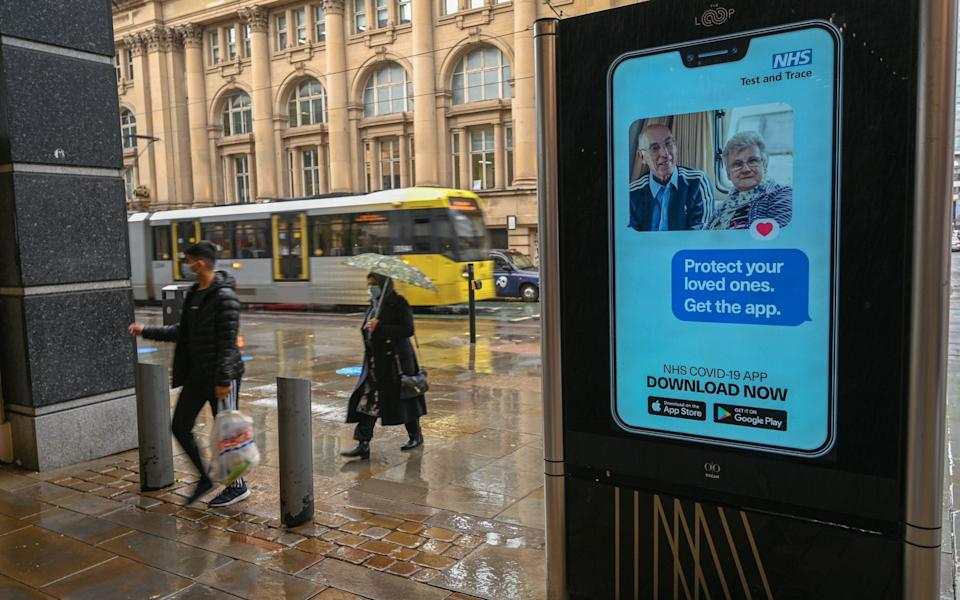 People walk past an electronic sign reminding pedestrians to download the NHS Test and Trace COVID-19 app in Manchester - Paul Ellis/AFP