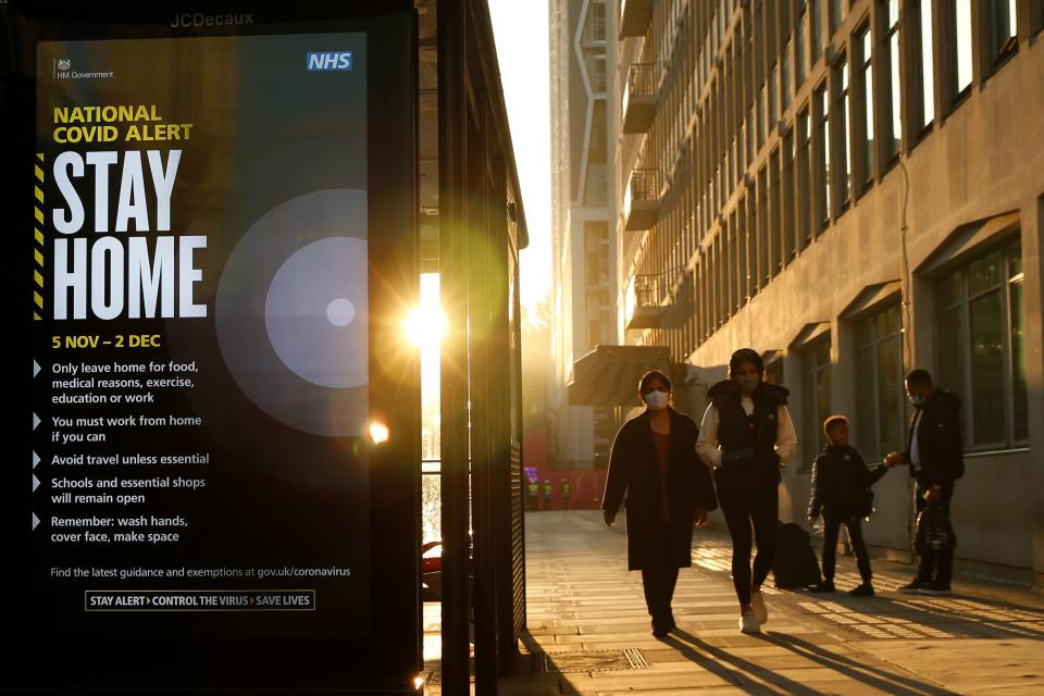Pedestrians wearing face masks pass a digital display showing the new measures required as England enters a second coronavirus lockdown in central London on November 5, 2020. (Photo by Hollie Adams / AFP) (Photo by HOLLIE ADAMS/AFP via Getty Images)