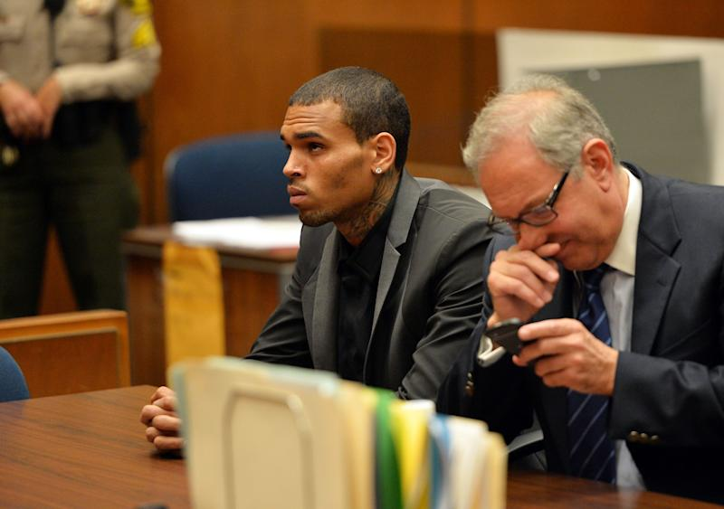 R&B singer Chris Brown, left, and his Attorney Mark Geragos appear during a court hearing at Los Angeles Superior court in Los Angeles Monday, July 15, 2013. A Los Angeles judge has revoked Chris Brown's probation after reading details of an alleged hit-and-run accident and his behavior afterward, but the singer was not ordered to jail. The prosecutor did not ask for Brown to be jailed. Another hearing is set for Aug. 16. The singer has been on felony probation in the 2009 beating of former girlfriend Rihanna. (AP Photo/Alberto E. Rodriguez, Pool)