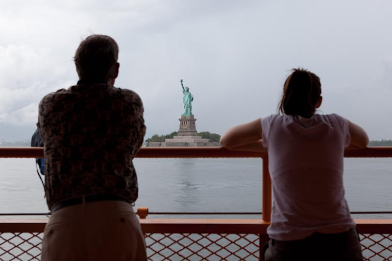 FILE - In this Aug. 27, 2011 file photo, Staten Island ferry passengers look out at the Statue of Liberty in New York. The Statue of Liberty, which has been closed to visitors since Superstorm Sandy, is scheduled to reopen for tours July Fourth, when Statue Cruises resumes departures for Liberty Island from Lower Manhattan. For tourists who want a photo of the famous statue without visiting the island, there are many options and vantage points, including rides on the free Staten Island Ferry. (AP Photo/John Minchillo, file)