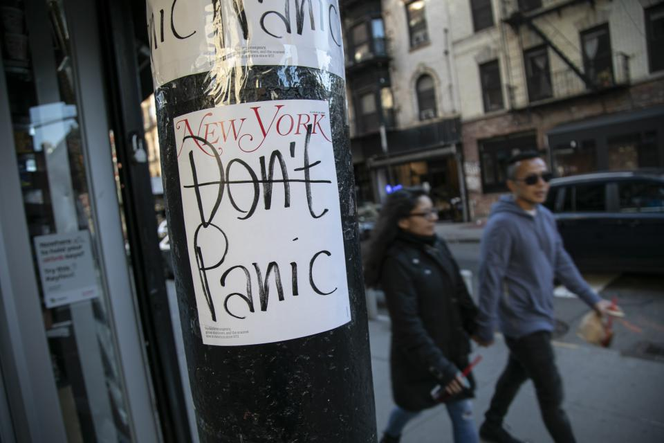 People walk past a convenience store where the latest cover of a magazine is stuck on a pillar outside of it on Sunday, March 15, 2020, in New York City. (AP Photo/Wong Maye-E)