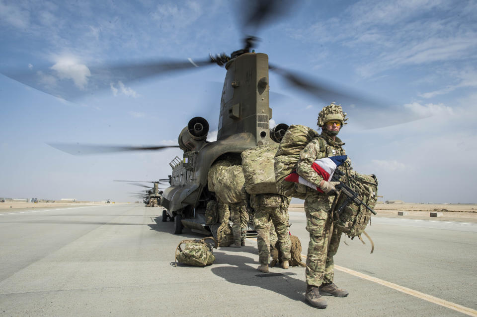 Wing Commander Matt Radnall, Officer Commanding 7 Force Protection Wing, carries a carefully folded Union Flag as the very last British troops board the last Chinook helicopter to leave Camp Bastion, Helmand Province, Afghanistan, as UK and Coalition forces carry out their Tactical Withdrawal finally leaving the base and handing it over to Afghan National Army.