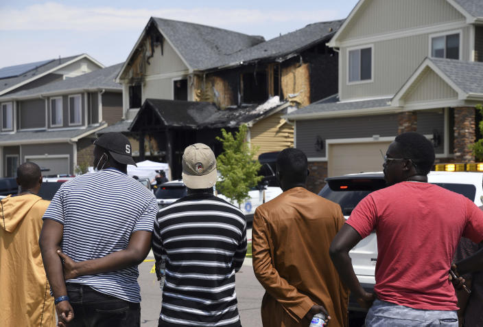 People look at a house where five people were found dead after a fire, in suburban Denver on Wednesday, Aug. 5, 2020. Three people escaped the fire by jumping from the home's second floor. Investigators believe the victims were a toddler, an older child and three adults. Authorities suspect was intentionally set. (AP Photo/Thomas Peipert)