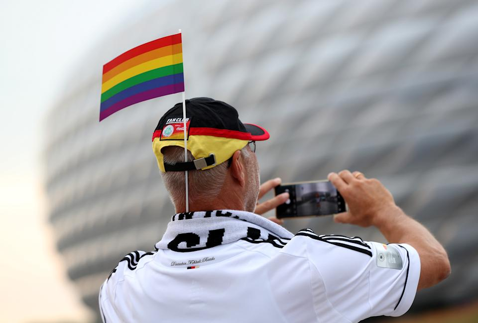 UNSPECIFIED, GERMANY - JUNE 23: A fan of Germany with a rainbow flag takes a phoograph in front of the Allianz Arena soccer stadium ahead of the Euro 2020 Group F match between Germany and Hungary on June 23, 2021 in Munich, Germany during EURO 2020.  (Photo by Alexandra Beier/Getty Images)