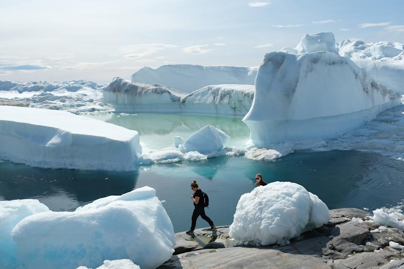 Visitors walk among free-floating ice jammed into the Ilulissat Icefjord during unseasonably warm weather near Ilulissat, Greenland. (Photo: Sean Gallup/Getty Images)