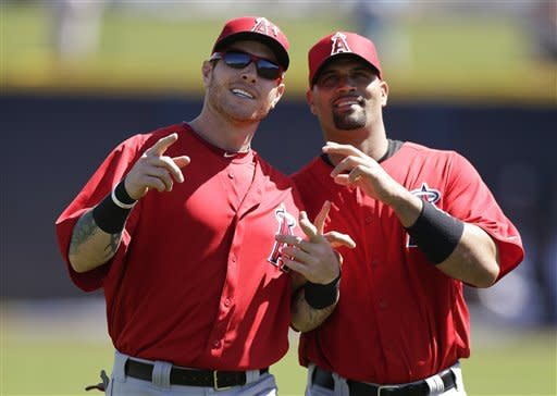 Los Angeles Angels left fielder Josh Hamilton, left, and first baseman Albert Pujols joke around before the Angels faced the San Diego Padres in a spring training baseball game Wednesday, March 13, 2013, in Peoria, Ariz. (AP Photo/Gregory Bull)