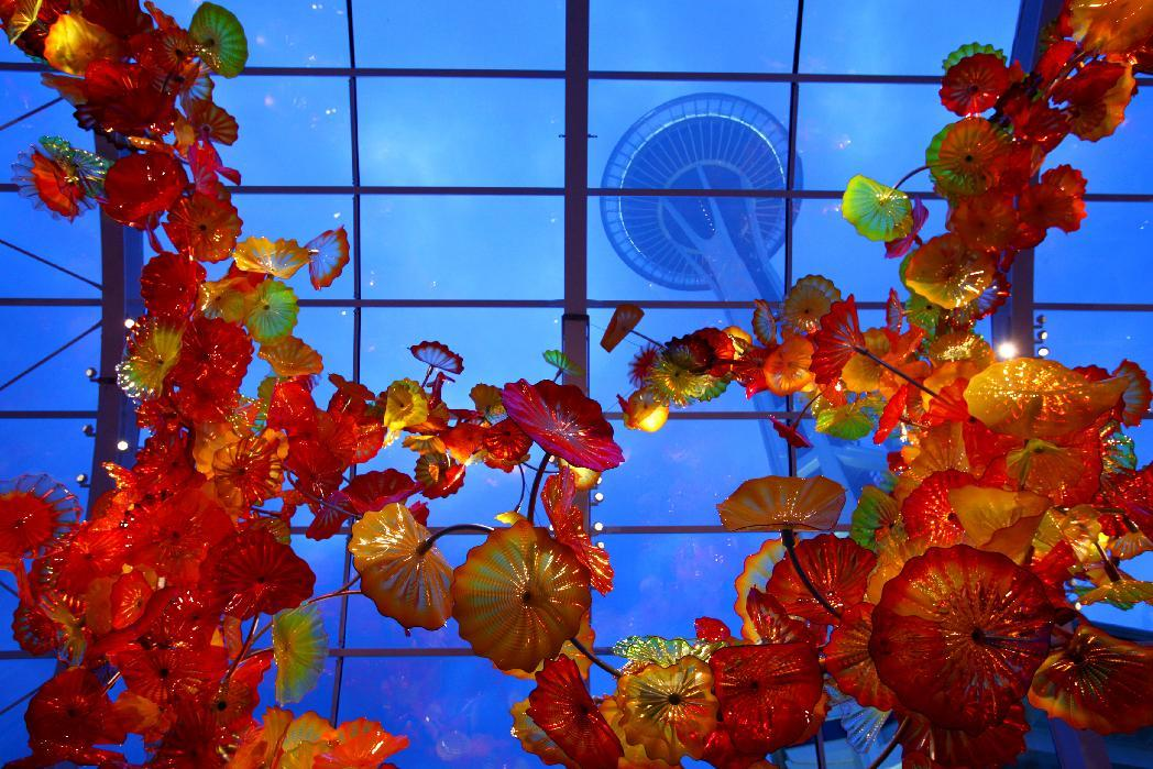 In this May 16, 2012 photo, the Space Needle towers over the Glasshouse at the new Dale Chihuly Garden and Glass museum at the Seattle Center. Fifty years after the World's Fair inserted the Space Needle into Seattle's skyline, the city is celebrating that anniversary by offering an array of new things to see and do at Seattle Center: from a zip line to the new art glass museum.(AP Photo/seattlepi.com, Joshua Trujillo) MAGS OUT; NO SALES; SEATTLE TIMES OUT; MANDATORY CREDIT; TV OUT