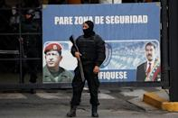 Members of the Bolivarian National Intelligence Service (SEBIN) stand guard next to a banner with the images of Venezuela's President Nicolas Maduro and Venezuela's late President Hugo Chavez, outside a detention center, where a riot occurred, according to relatives, in Caracas, Venezuela May 16, 2018. REUTERS/Carlos Garcia Rawlins