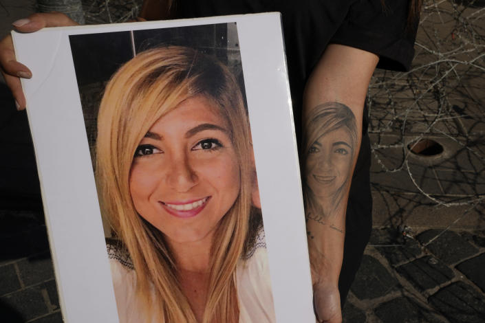 Mariana Fodoulian shows a tattoo and a portrait of her late sister Gaya Fodoulian during a protest near the parliament building to demand an expedited investigation, in Beirut, Lebanon, Sunday, July 4, 2021. Gaya Fodoulian died during the Aug. 4, 2020, Beirut port explosion. A year after the blast, families of the victims are consumed with winning justice for their loved ones and punishing Lebanon's political elite, blamed for causing the disaster through their corruption and neglect. Critics say the political leadership has succeeded so far in stonewalling the judicial investigation into the explosion. (AP Photo/Hassan Ammar)