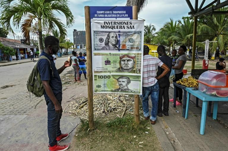 A migrant in Necocli studies a billboard advertising how to invest money locally