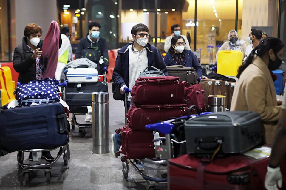 Passengers wearing protective face masks wait to exit upon arrival at Chhatrapati Shivaji Maharaj International Airport after India cancelled all flights from the UK over fears of a new strain of the coronavirus disease (COVID-19), in Mumbai, India, December 22, 2020. REUTERS/Francis Mascarenhas