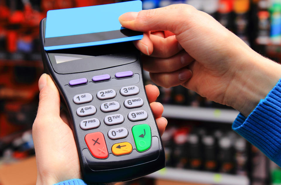 Hand of woman paying with contactless credit card with NFC technology in shop, cashless paying for shopping or products concept (Hand of woman paying with contactless credit card with NFC technology in shop, cashless paying for shopping or products co