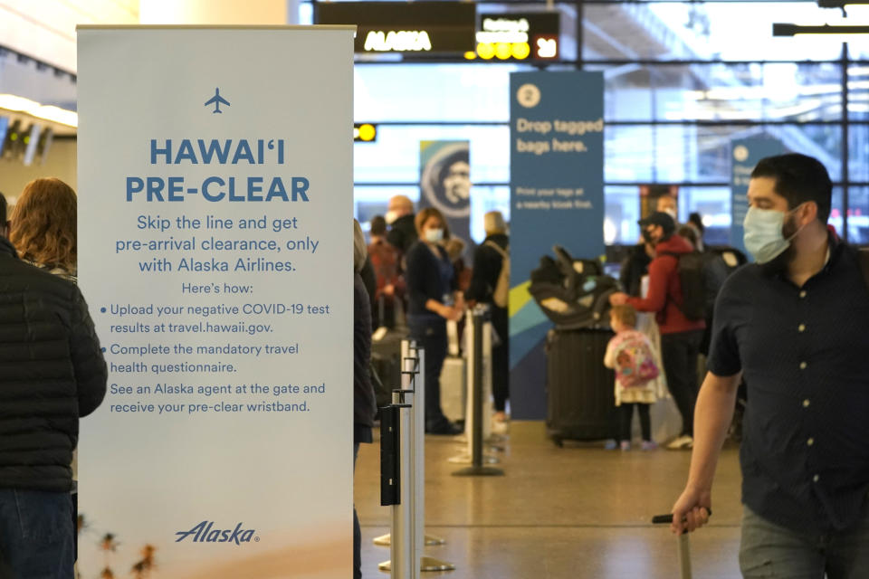 Passengers walk past an Alaska Airlines sign with information on providing COVID-19 test information before flying to Hawaii, Monday, March 1, 2021, at Seattle-Tacoma International Airport in Seattle. (AP Photo/Ted S. Warren)