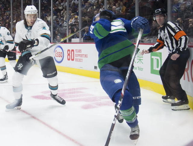 San Jose Sharks defenseman Brenden Dillon (4) high-sticks Vancouver Canucks right wing Jake Virtanen (18) during the second period of an NHL hockey game Saturday, Jan. 18, 2020, in Vancouver, British Columbia. (Jonathan Hayward/The Canadian Press via AP)