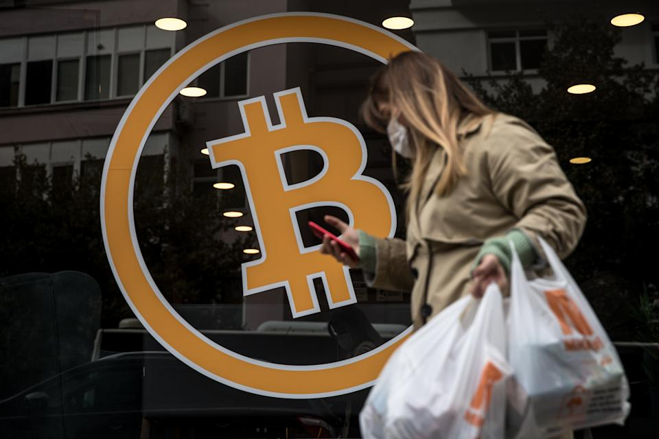 A woman walks past the entrance of a cryptocurrency exchange office in Istanbul, Turkey. Photo: Chris McGrath/Getty Images