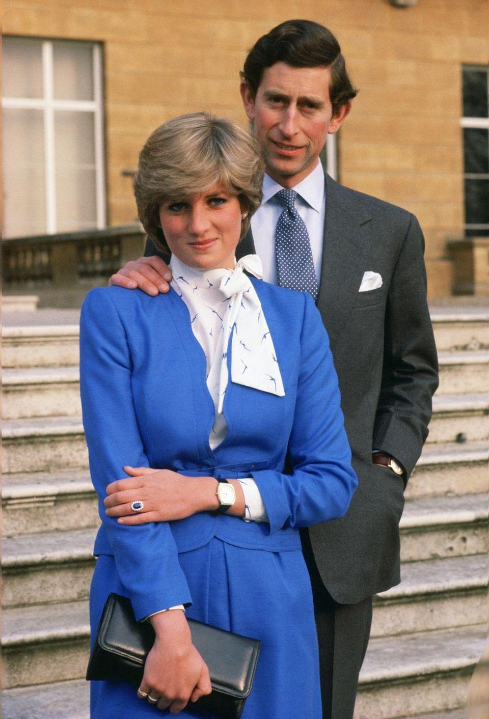"""<p>Lady Diana Spencer—later known as Diana, Princess of Wales—and Prince Charles pose outside Buckingham Palace to celebrate their engagement. The bride-to-be flaunts <a href=""""http://www.bbc.com/news/world-south-asia-13214228"""" rel=""""nofollow noopener"""" target=""""_blank"""" data-ylk=""""slk:her ring"""" class=""""link rapid-noclick-resp"""">her ring</a>, featuring an oval sapphire surrounded by blue diamonds.</p>"""