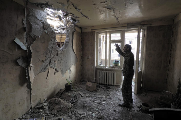 A man gestures in an apartment damaged by shelling by Azerbaijan's artillery during a military conflict in Stepanakert, the separatist region of Nagorno-Karabakh, Tuesday, Nov. 3, 2020. Fighting over the separatist territory of Nagorno-Karabakh entered sixth week on Sunday, with Armenian and Azerbaijani forces blaming each other for new attacks. (AP Photo)